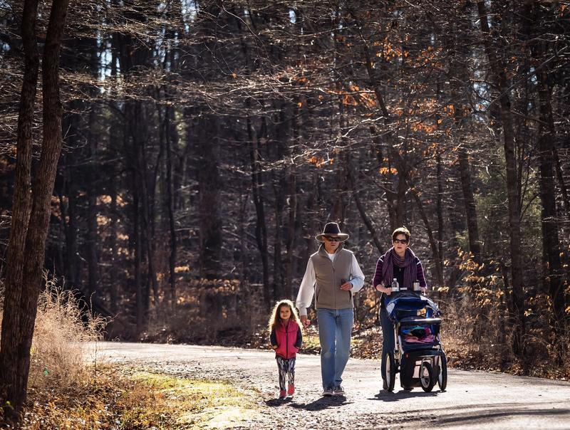 A family takes a stroll on the Reedy Creek Trail at William B. Umstead State Park.