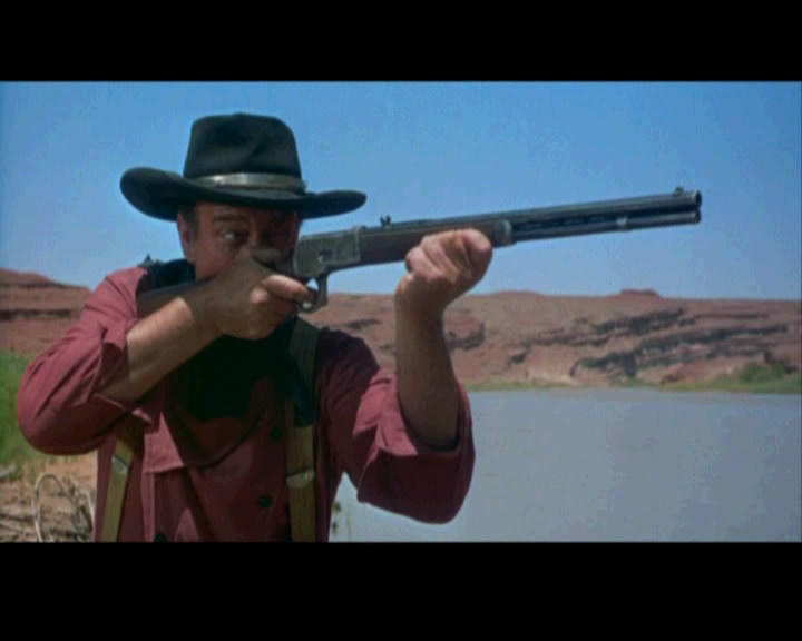 Actor John Wayne aims his gun in the 1956 Western film 'The Searchers' by John Ford.
