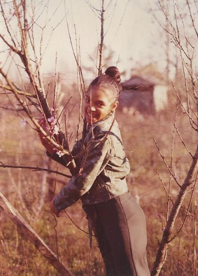 Phyliss Craig leaning on the peach tree on the edge of the family farm in 1970.