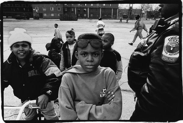Image of young black kids in Chicago with a police officer.
