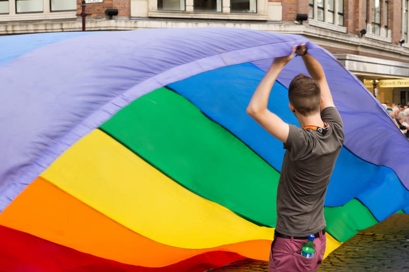 a young man holding a pride flag