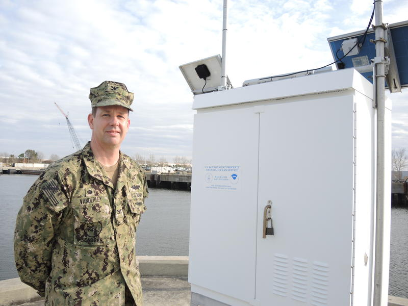 Capt. Dean VanderLey, commanding officer of Naval Facilities Engineering Command for the Mid-Atlantic region, standing in front of NOAA's Sewell's Point tidal gauge, which measures the sea level at Naval Station Norfolk, the world's largest naval base.