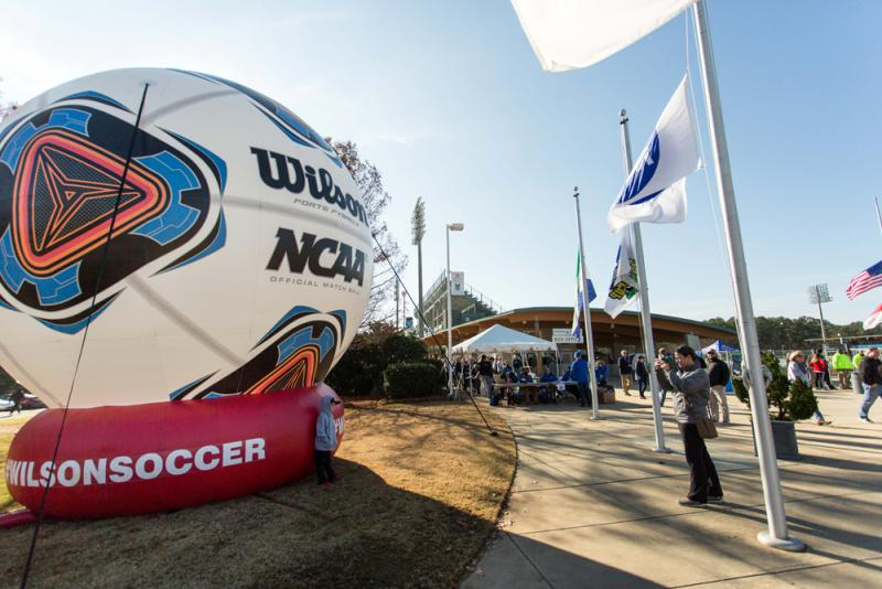 A young soccer fan poses for a photo in front of a giant inflatable soccer ball outside of WakeMed Soccer Park prior to the NCAA Women's College Cup final between Penn State and Duke in Cary, N.C., Sunday, Dec. 6, 2015.