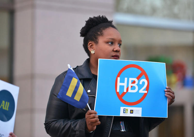Cassandra Thomas of Human Rights Campaign holds a sign advocating the repeal of HB2 as Executive Director Chad Griffin, President of Human Rights Campaign and Executive Director of Equality NC, Chris Sgro, discuss the North Carolina election results.