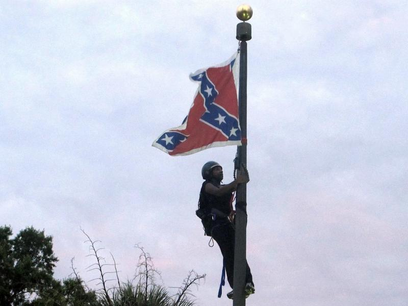 In this June, 27, 2015, file photo, Bree Newsome of Charlotte, N.C., climbs a flagpole to remove the Confederate battle flag at a Confederate monument in front of the Statehouse in Columbia, S.C.