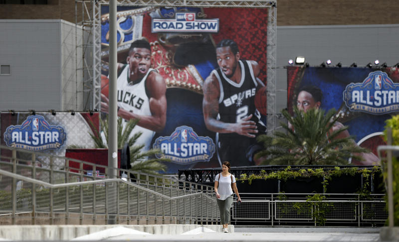 Rachel Seibel walks past signage being put up in preparation for the NBA All Star Game festivities this weekend, in New Orleans, Tuesday, Feb. 14, 2017. Charlotte won't be a ghost town this weekend, but it sure won't be buzzing like many had hoped.