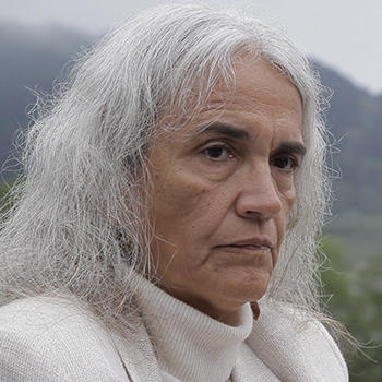 slim, white-haired Abby Abinanti stands looking serious on a misty hill