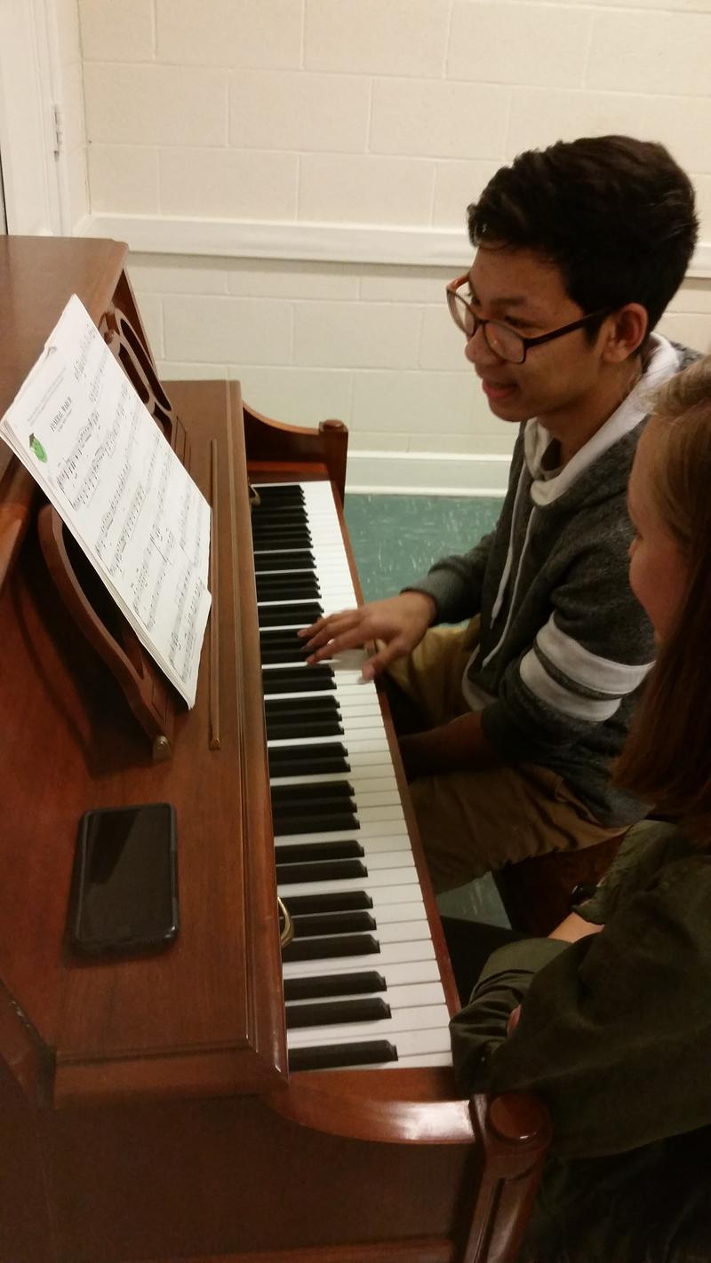 Joshua Pongsitiphon (left) works on a new piece of music with Musical Empowerment volunteer Katharine Batchelor. The fifteen-year-old has been taking free private piano lessons with Batchelor for nearly seven years.