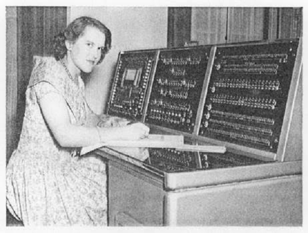 Andrina Wood, an early computer expert in 1958, sits at the console of a BTM computer.