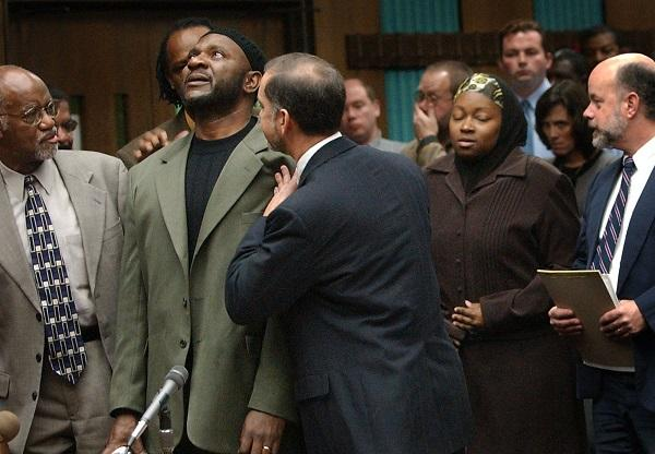 Darryl Hunt with lawyers Mark Rabil (R) and James Ferguson, reacts to a judge dropping murder charges against him at a hearing in 2004.