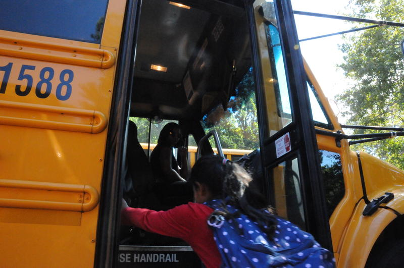 Wake County bus driver Auh Murel Wright greets a student before the afternoon trip home. Wright is among many school-based employees who struggle to make ends meet on their current salaries.