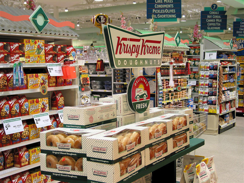 A supermarket display of Krispy Kreme Doughnuts and other junk food.