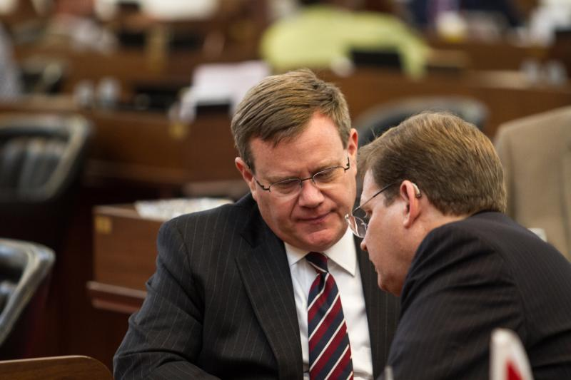 Speaker of the House Tim Moore (left) converses with Representative Nelson Dollar (right) during a break on debate of the state budget at the State Capitol on June 21, 2017.