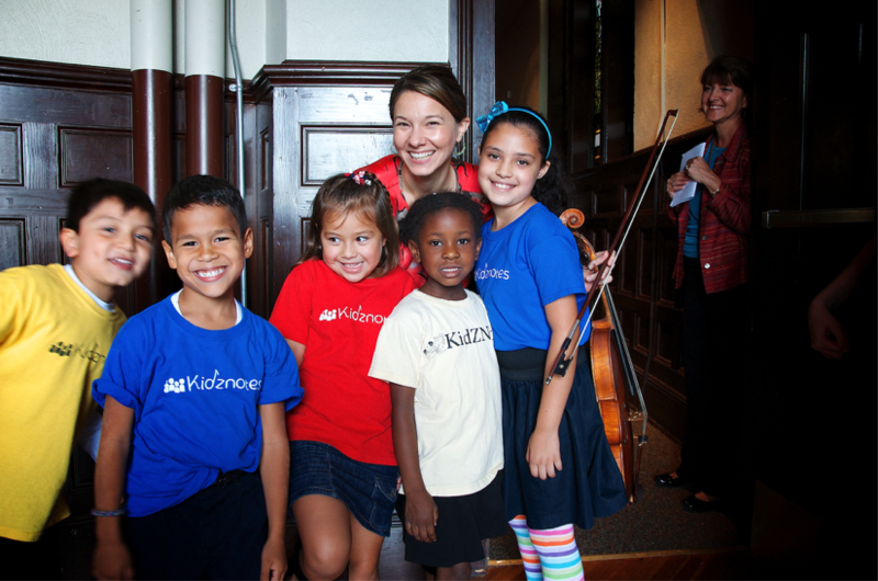 Katie Wyatt poses with children from the program she co-founded, Kidznotes.