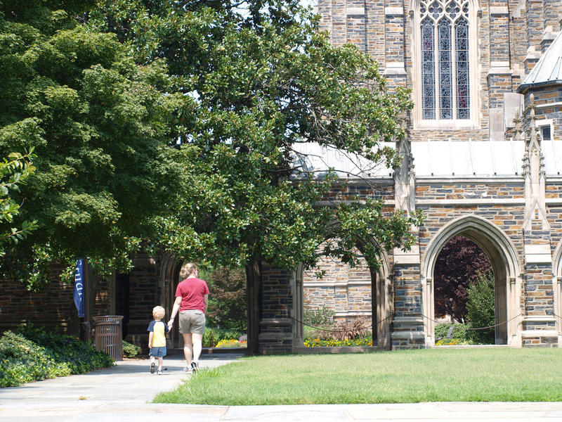 a woman and child walking at the Duke University campus.