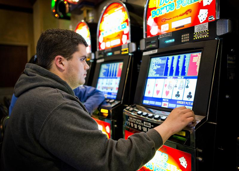 a man sitting at a video poker machine