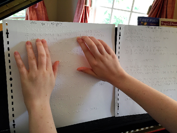 Mikels reads the lyrics of a song in braille. It normally takes about two weeks to order and receive the songs she wants to sing in braille.