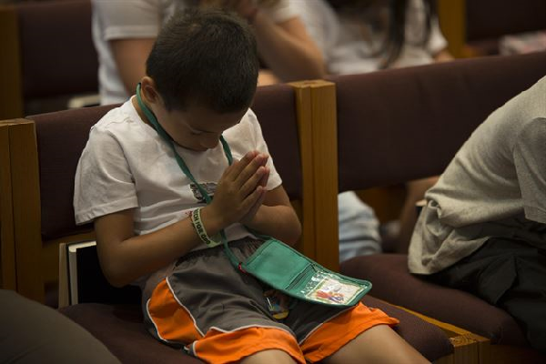 Child prays at vacation bible school.