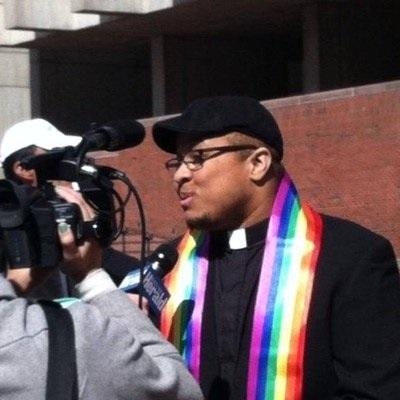 Reverend Mykal Slack wears a rainbow stole while speaking with the press.