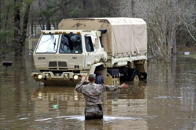 Army Sgt. David Breaud directs a high water vehicle down a flooded roadway.