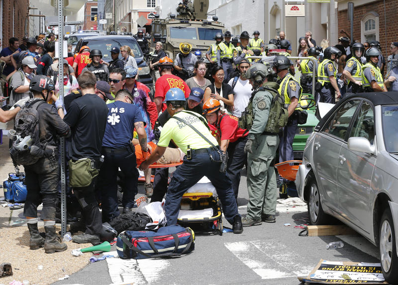 Rescue personnel help injured people after a car ran into a large group of protesters after a white nationalist rally in Charlottesville, Va., Saturday.