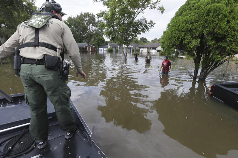 U.S. Border Patrol Agent Steven Blackburn, left, checks if people wading in water need help during a search a rescue operation in a neighborhood inundated by floodwaters from Tropical Storm Harvey in Houston, Texas, Wednesday, Aug. 30, 2017.