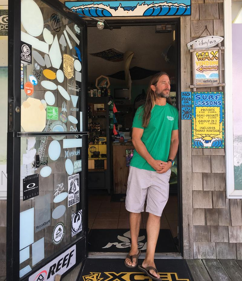 Jason Heilig stands in the doorway of Rodanthe Surf Shop on Hatteras Island, which he owns. He normally counts on the busy season for a big chunk of annual revenue.