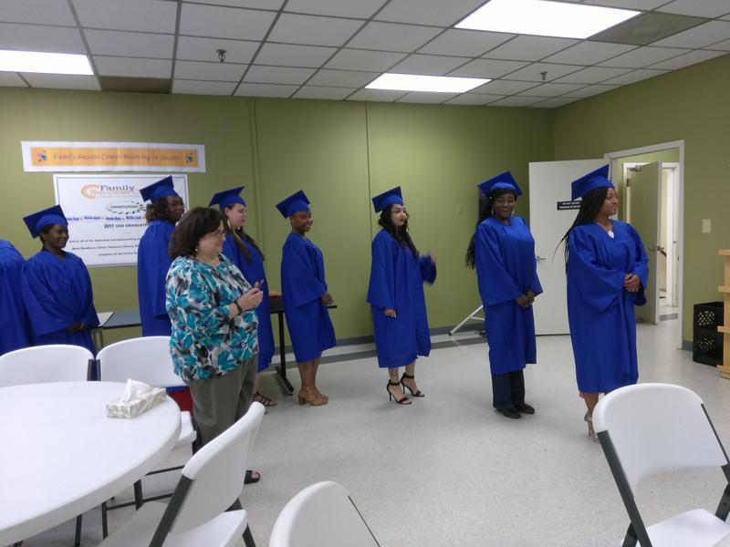 Line of women stand in graduation gowns.