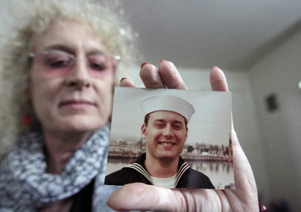 Autumn Sandeen, veteran, holds a picture of herself as a man and navy seaman recruit.