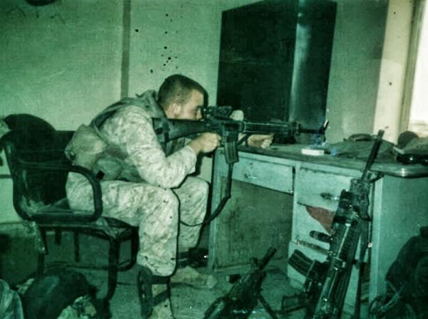 Thomas J. Brennan sits at the desk in Fallujah, Iraq, where he made his first kill shot. November, 2004.