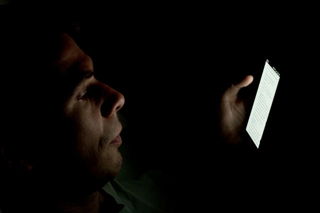 Man stares at phone in dark room.