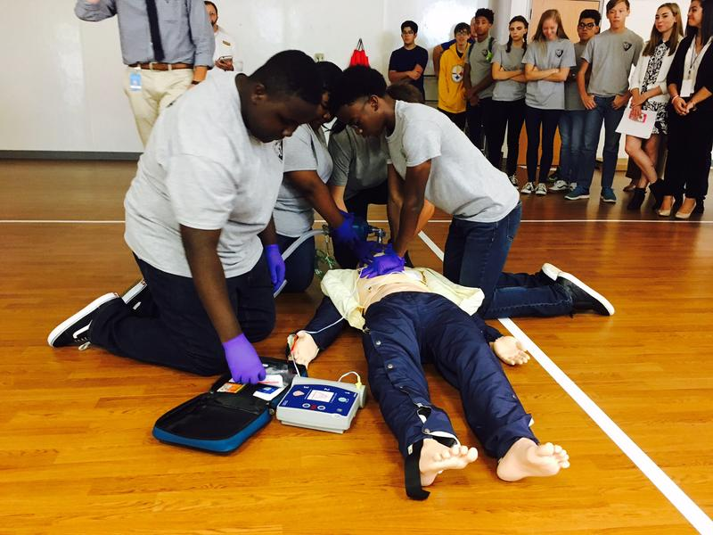 North Wake College & Career Academy students Emerson Bulluck, De'Asia Foster and Alabi Orisadele perform CPR on dummy during demonstration at the school's EMS rodeo.