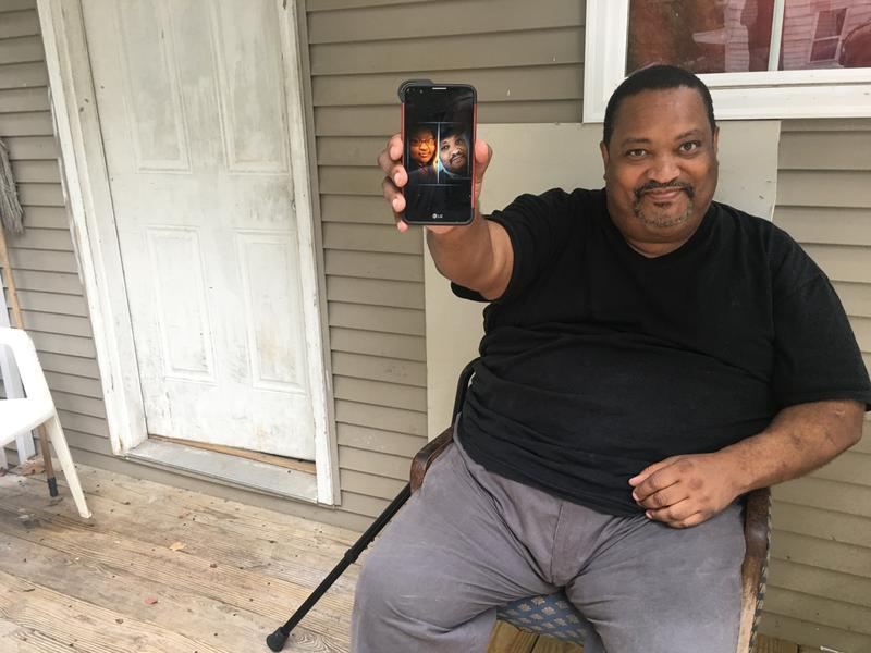 Darnell Wilson sits on his side porch and shows off a picture of his daughter.