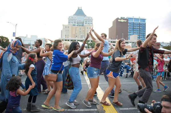 Folk festival goers dance in the streets