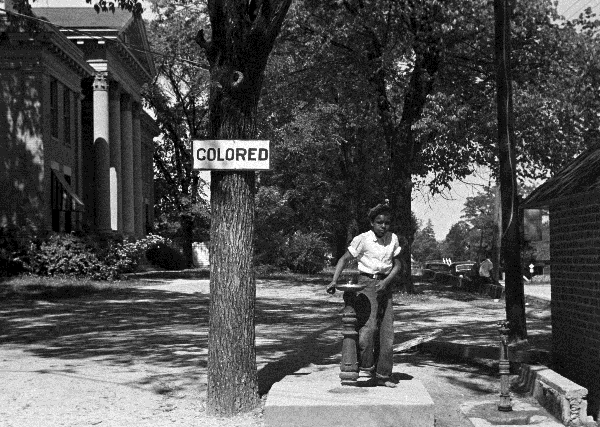 A young boy drinks from a segregated water fountain in front of a courthouse in Halifax, NC, 1938