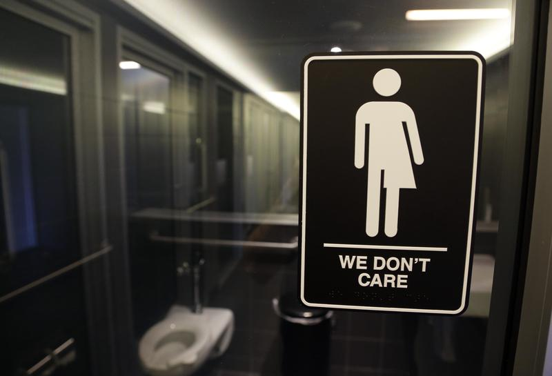 FILE - This Thursday, May 12, 2016, file photo, shows signage outside a restroom at 21c Museum Hotel in Durham, N.C. North Carolina is in a legal battle over a state law that requires transgender people to use the public restroom matching the sex on their