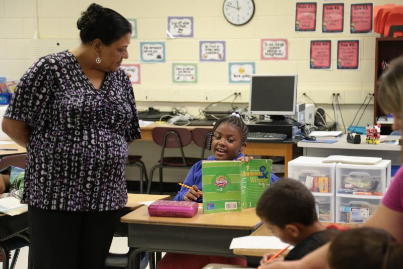 West Lumberton Elementary teacher June Hunt helps second grader Niveah Barnes with a grammar assignment in their temporary classroom at Lumberton Junior High. Flooding from Hurricane Matthew destroyed the home where NIveah was living.