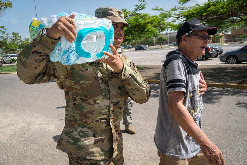PONCE, PUERTO RICO -  North Carolina National Guard SSG Joe Rodriguez carries donated water and MRE's for Nani Soto in a distribution center in a sports arena in the Southern town of Ponce, the 2nd largest city in Puerto Rico, on October 20, 2017.