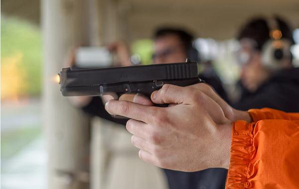 man holding gun at shooting range/gun club