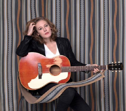 Tift Merritt and her guitar in front of her personally-designed textiles.