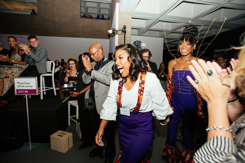 Designer Desiree Hedrick, middle, and model Anita Taylor walk to the stage after winning first prize during a fashion show for the kickoff of the exhibit, Inspiring Beauty: 50 Years of Ebony Fashion, at the North Carolina Museum of Art in Raleigh, N.C. He