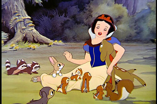 A screenshot from Disney's 1937 film Snow White shows Snow White surrounded by forest creatures.