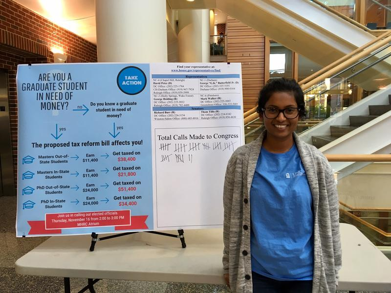 Kalyani Hawaldar stands in front of poster describing the tax plan's effect on graduate students.