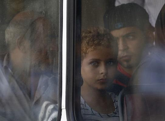 Palestinian-Syrian child Hamad Alroosan looks out of the window of a police bus after arriving at the Armed Forces of Malta Maritime Squadron base at Haywharf in Valletta's Marsamxett Harbour October 12, 2013.