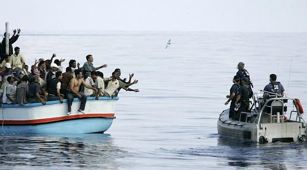 Armed Forces of Malta marines toss bottles of water to a group of around 180 immigrants as a rescue operation gets underway after their vessel ran into engine trouble, some 30km (19 miles) southwest of Malta September 25, 2005.