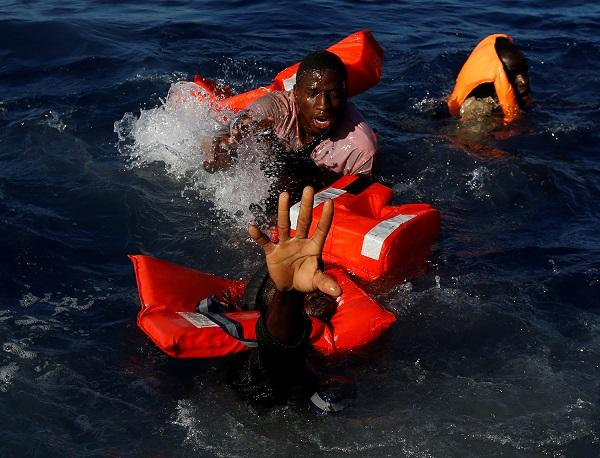 Migrants try to stay afloat after falling off their rubber dinghy during a rescue operation by the Malta-based NGO Migrant Offshore Aid Station (MOAS) ship in the central Mediterranean in international waters some 15 nautical miles off the coast of Zawiya