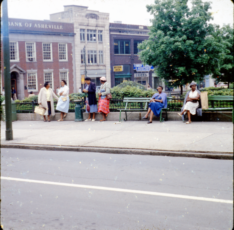 Women sitting at a bus stop.