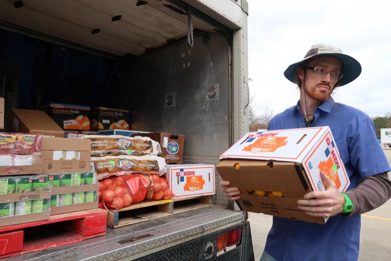 Man unloads truck of canned food and produce for food pantry