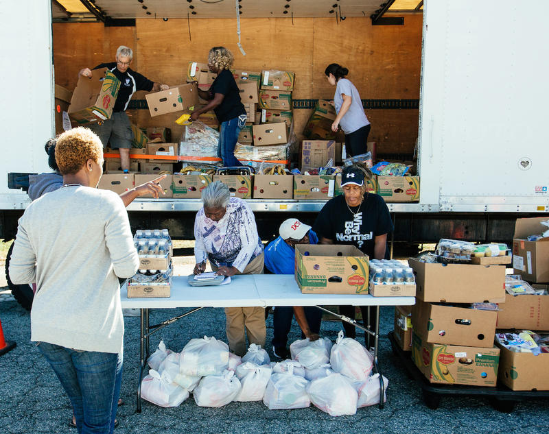 Volunteers and staff work during a fresh mobile market organized by Out of the Garden Project, a nonprofit food assistance program for Guilford County families in Greensboro, N.C. on Oct. 18, 2017.