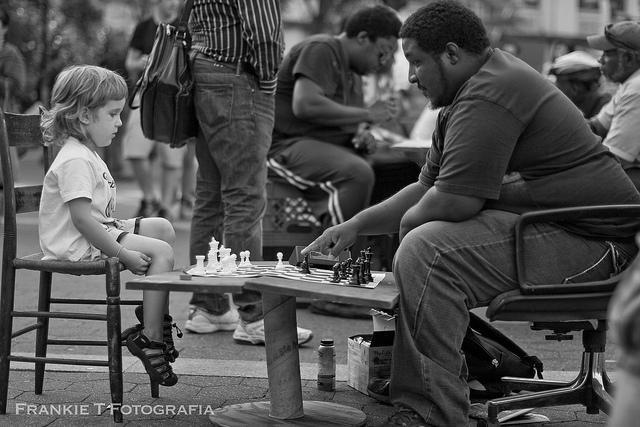 child and man playing chess outdoors